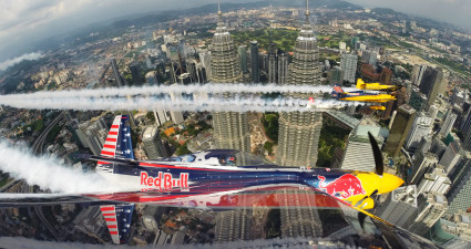 Kirby Chambliss of the United States flies in formation with Matt Hall of Australia, Yoshihide Muroya of Japan and Nigel Lamb of Great Britain prior to the third stage of the Red Bull Air Race World Championship in front of the Petronas Towers in Kuala Lumpur, Malaysia on May 15, 2014.